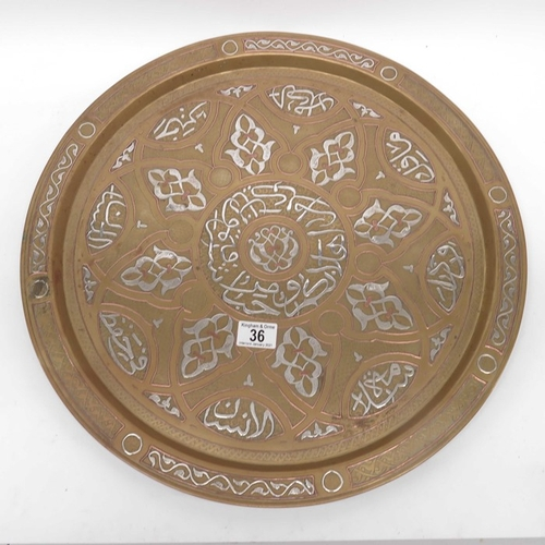 36 - A Cairo ware brass tray, silvered thuluth style script within central brass lined medallion within l...