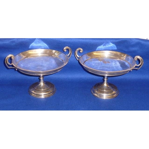 174 - A pair of hallmarked silver Tazzas, each with high scrolling pierced handle and raised on circular f...