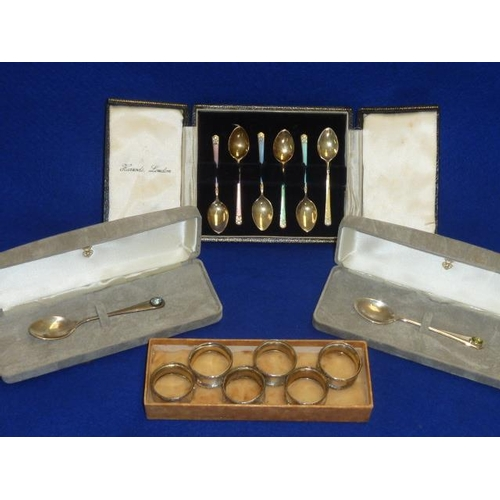 194 - A small assortment of silver to include two cased Coffee Spoons, each with a singular hand cut semi-...