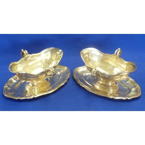195 - A pair of 18th Century style two-handled boat-shaped Sauce Boats on conforming stands, the finely ca...