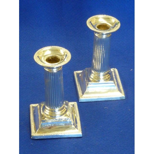 198 - A pair of hallmarked silver (weighted) Table Candlesticks of column form, 13cm high, London assay ma...