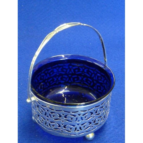 221 - A hallmarked pierced cylindrical silver Sugar Basket with swing handle, blue glass liner and raised ...