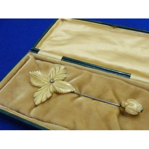 254 - A gilt tooled green leather Case containing a carved ivory stick Brooch modelled as a flower head, e...
