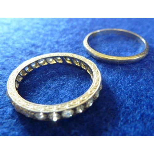 257 - A platinum band (approx. 3.33g) together with an engraved white metal Eternity Ring set with white s...