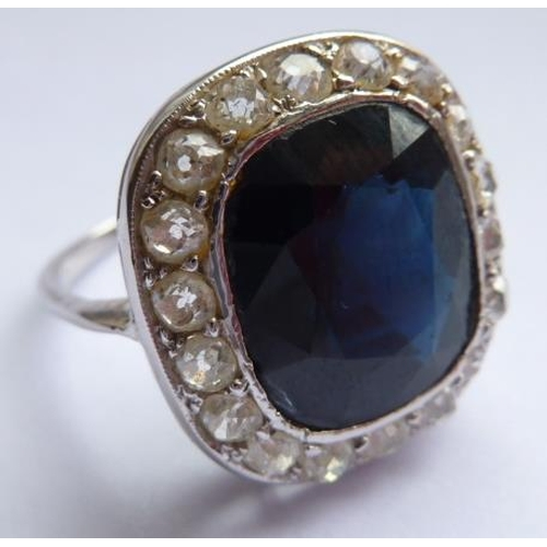 269 - A ladies very fine white metal Dress Ring centrally set with a large hand cut sapphire within a diam...