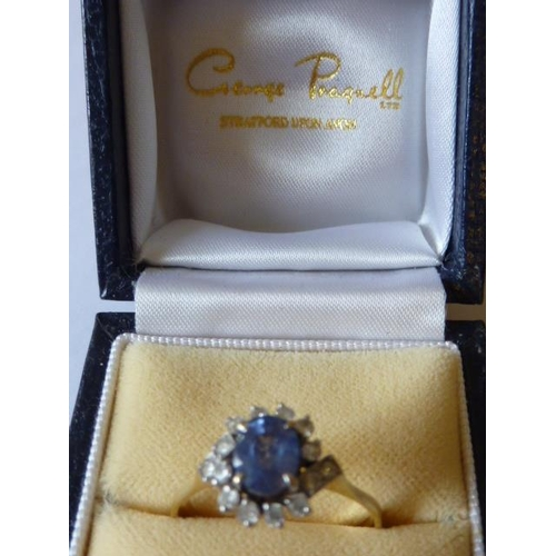 271 - A ladies 9 carat yellow gold Dress Ring, the central light blue hand cut oval stone surrounded by fu...