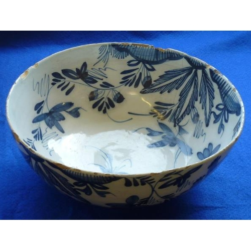 29 - An 18th Century Delftware Bowl hand decorated in cobalt blue with various flower heads and leaves et...
