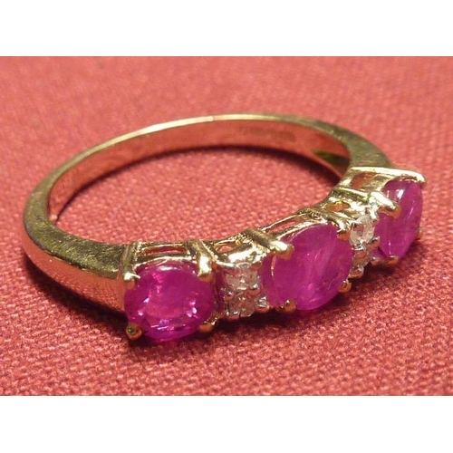 292 - A 9 carat gold ladies Ring set with three rubies and four small diamonds...
