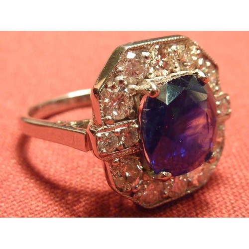 299 - A magnificent 18 carat white gold Ring, the central 5 carat sapphire surrounded by 14 fine white dia...