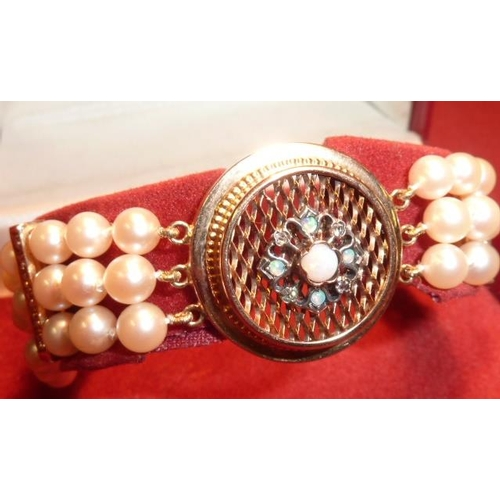 304 - A fine three strand pearl and diamond Bracelet with 18 carat gold opal and diamond circular centre p...