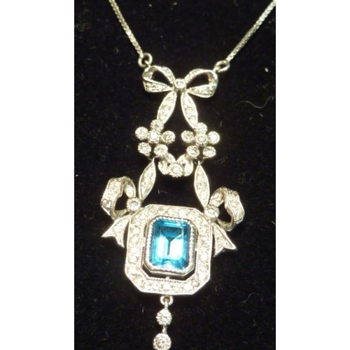 309 - An 18 carat white gold topaz and diamond Necklace on a 9 carat Chain...