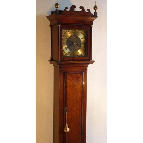 334 - A George III period oak cased eight-day Longcase Clock, the wavy style pediment flanked by two brass...