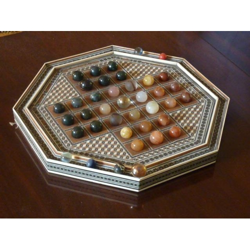 470 - An octagonal bone and wood inlaid Solitaire Board having a variety of various coloured glass marbles...