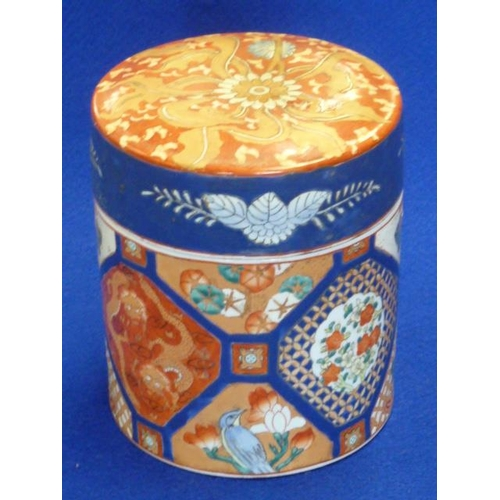 55 - A late 19th Century Japanese cylindrical porcelain Jar and Cover hand decorated in the Imari palette...