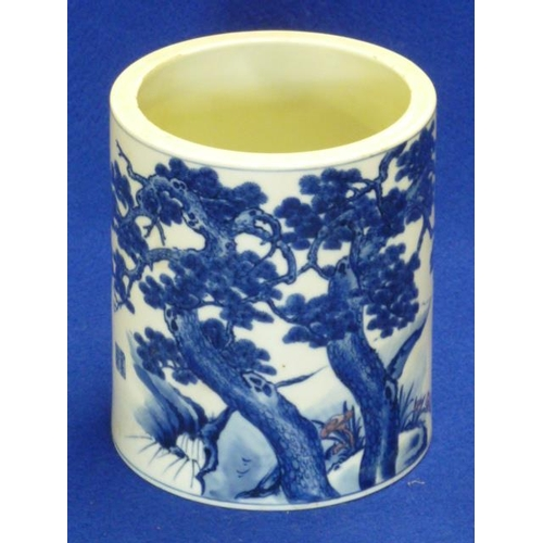 61 - A Chinese cylindrical porcelain Brush Pot hand decorated in underglaze blue with two pine trees agai...