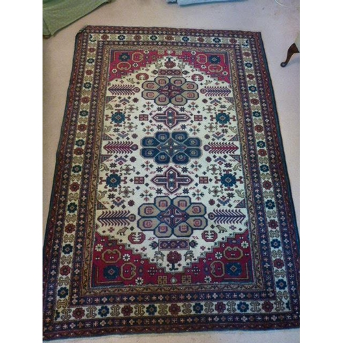 639 - A hand knotted Persian style Rug, three central lozenge motifs against a larger cream lozenge and re...