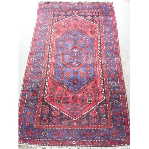 645 - A hand knotted Persian Carpet, the central blue lozenge with stylised patterns within a larger red l...
