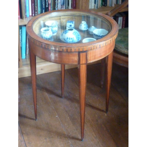 665 - A late 19th/early 20th Century circular satinwood Bijouterie Table, the glazed top above four square...