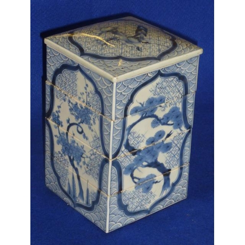 87 - A Chinese porcelain four-  sectional lidded Tower hand decorated in underglaze blue with pine trees,...
