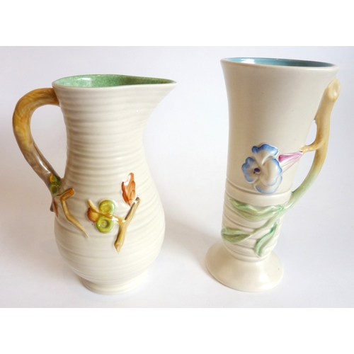 23 - A mid-20th century Clarice Cliff pottery vase hand-decorated in relief with a flower head, the handl...