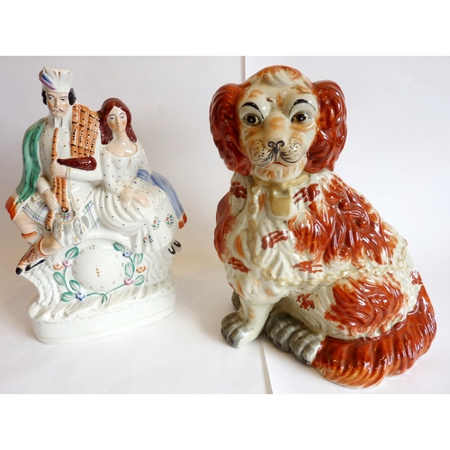 30 - An extra large Victorian Staffordshire spaniel and a Staffordshire clock figure of a couple...