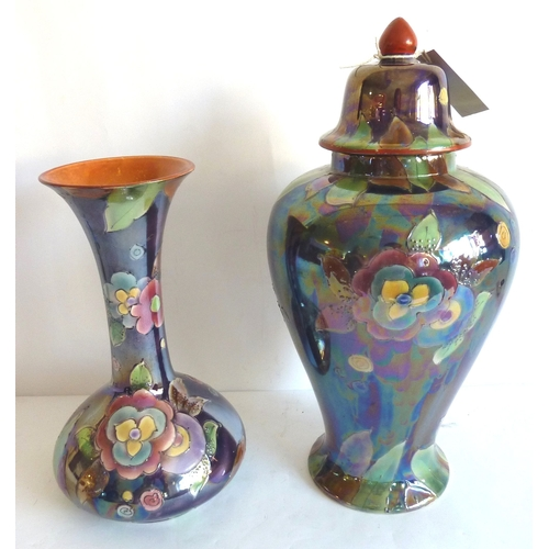 7 - A bottle-shaped early-20th century ceramic vase decorated with flowers together with one other simil...