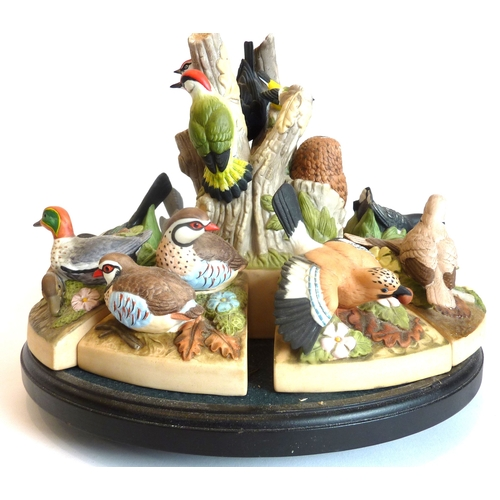 12 - A set of twelve fine bone-china bird figures with rotating display stand (some damage)...