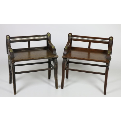 A pair of Victorian oak Hall Chairs, by Jas. Schoolbred & Co., each with open brass pierced gallery backs over swept arms with brass mounts, on front sabre legs. (2)