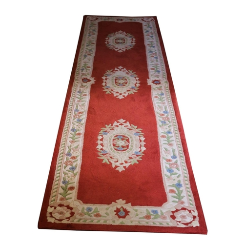 41 - <strong>A set of three red/pink ground woollen Runners,</strong> each with a cream ground floral bor...