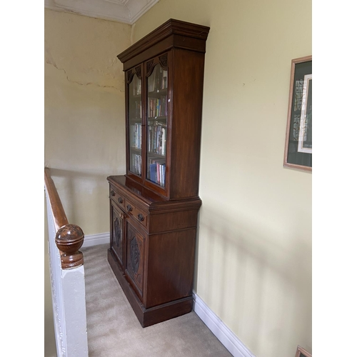 1 - An Edwardian walnut Bookcase, with two upper glazed doors and two frieze drawers above two carved pa...