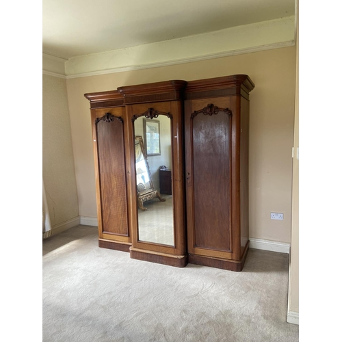 13 - A fine Victorian mahogany breakfront Wardrobe, with moulded cornice above a centre mirror door and a...