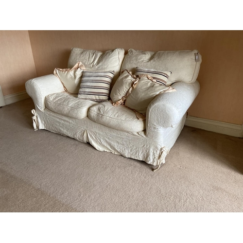 19 - A two seater Easy Settee, covered in ivory fabric and loose cushions, 68'' (172cms). (1)...