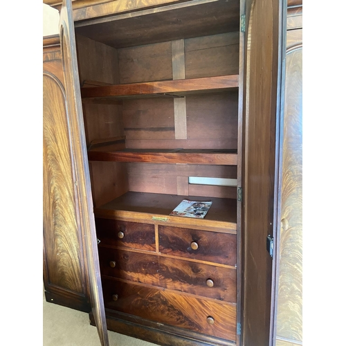 20 - A fine Victorian breakfront Wardrobe, with raised centre and moulded cornice above four arched doors...