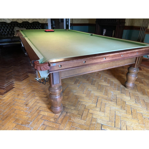 241 - A full size Billiard / Snooker Table, in mahogany and covered in green baize raised on 8 heavy turne...