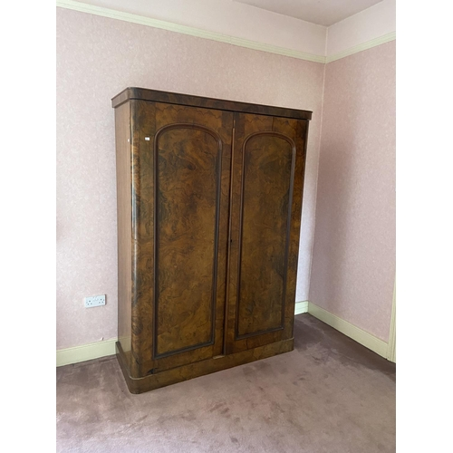 48 - A Victorian figured walnut Wardrobe, with arched panel doors on plinth base, 81'' x 55'' (206cms x 1...