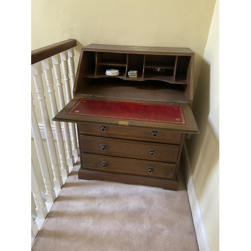 7 - A 17th Century style oak slope front Bureau, with linen fold panels above four long drawers on brack...