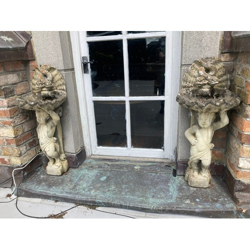113A - A pair of composition stone Garden Cherub Bird Baths, with shell bowls and double dolphin crests, 38...