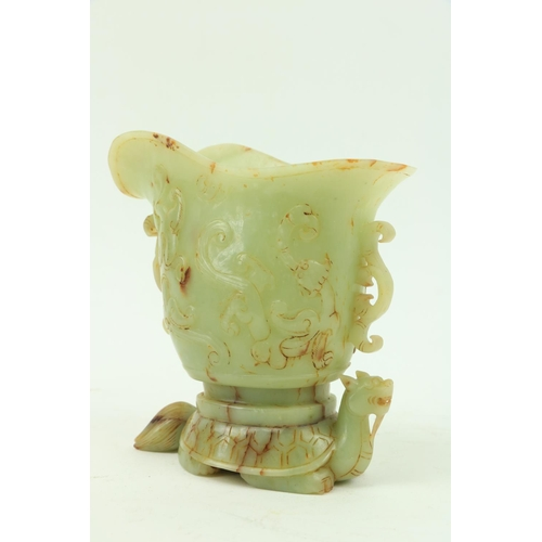 29 - A fine carved Chinese jade Libation Cup, carved in relief with scrolls under a double spout and two ...