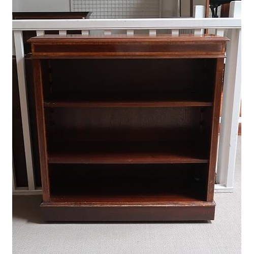 43 - A mahogany and satinwood crossbanded open bookcase raised on bracket feet, 102 cms high, 96 cms wide...