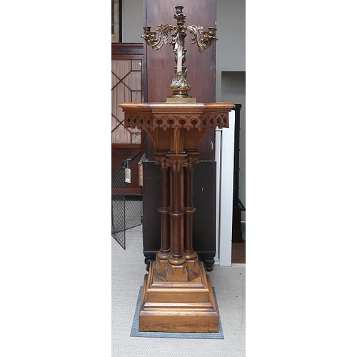 19 - A Victorian Puginesque style pitch pine octagonal torchere on stepped plinth base, 136 cms high.