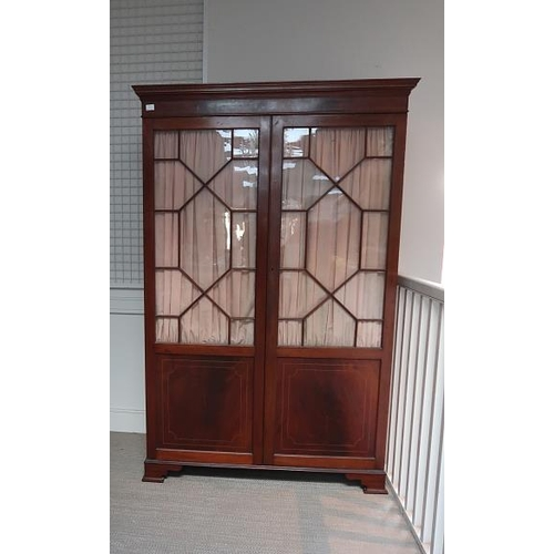 27 - An Edwardian Sheraton style inlaid mahogany twin astragal glazed panel door wardrobe, 196 cms high, ...