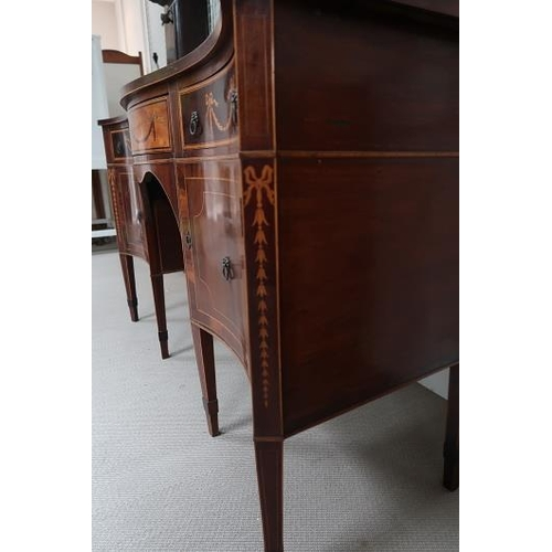 54 - A George III revival mahogany and satinwood serpentine sideboard, the frieze with three drawers deco...