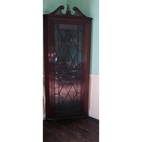 57 - A late Georgian mahogany corner cabinet, broken swan neck pediment above glazed door, raised on brac...