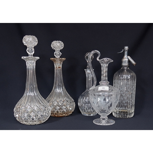 46 - A pair of moulded glass decanters and stoppers, an etched glass claret jug, a soda syphon and one ot...