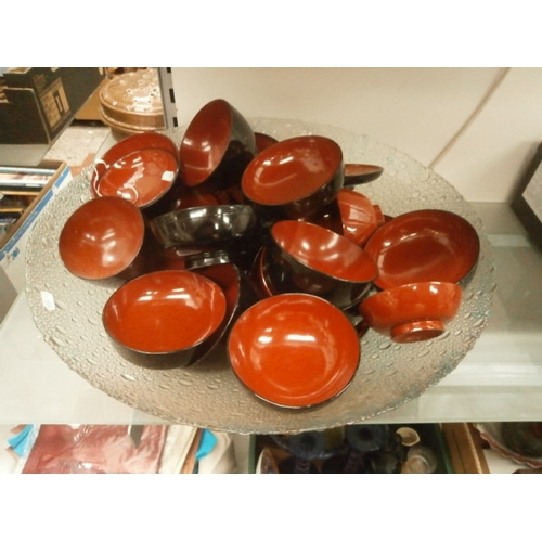 449 - Large glass bowl containing lacquered bowls...