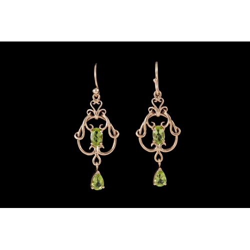 21 - A PAIR OF PERIDOT DROP EARRINGS, mounted on 9ct gold...