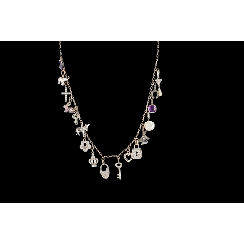 58 - A DIAMOND SET CHARM NECKLACE, with seventeen diamond, amethyst and mother of pearl set charms, on 14...