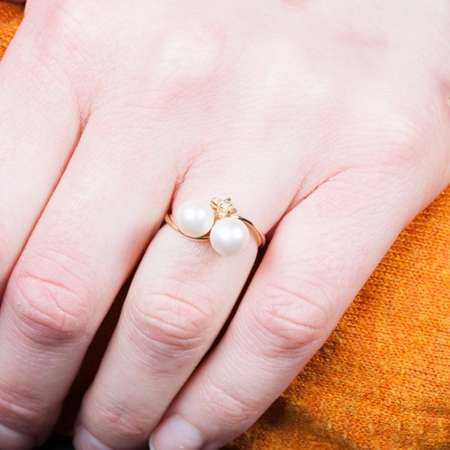 10 - A PEARL AND DIAMOND CROSSOVER RING, mounted in 18ct yellow gold. Size K....