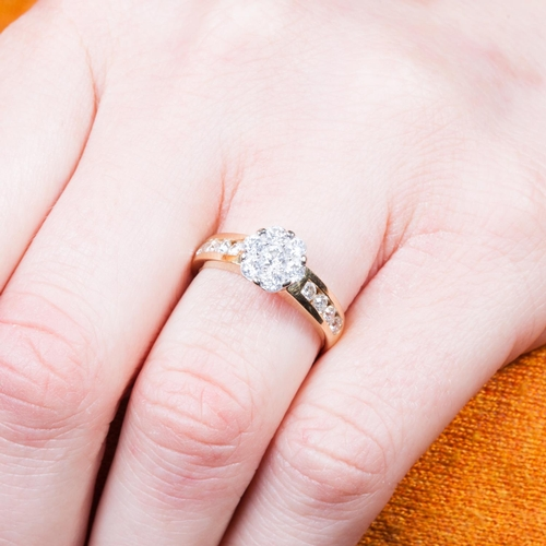 18 - A DIAMOND DAISY CLUSTER RING, mounted in 18ct yellow gold, with diamond channel set shoulders, size ...