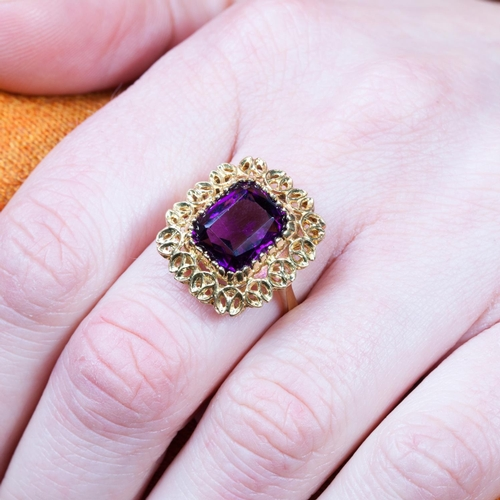 28 - AN AMETHYST SINGLE STONE RING, the trap cut amethyst to a yellow gold open worked mount...